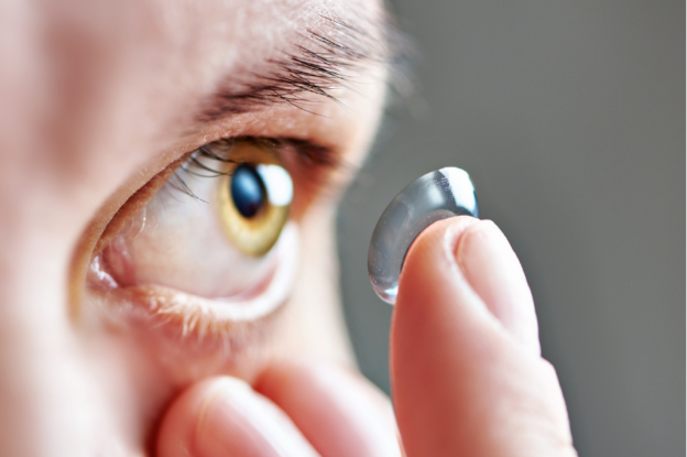 person putting a contact lens in their eye